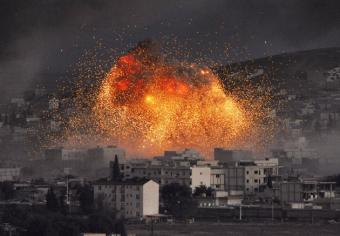 An explosion rocks Kobani during a reported suicide car bomb attack by ISIS.